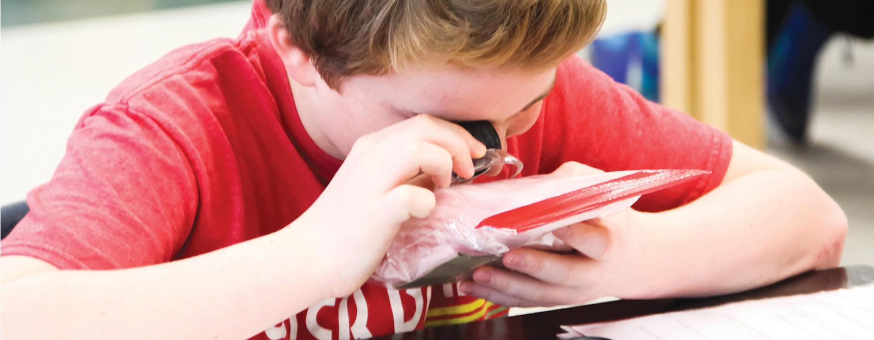 Boy looks at insulation material through loupe in Home Heat Transfer workshop