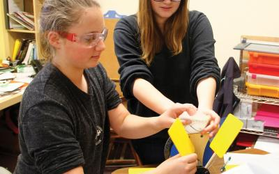 Two girls work with a model wind turbine
