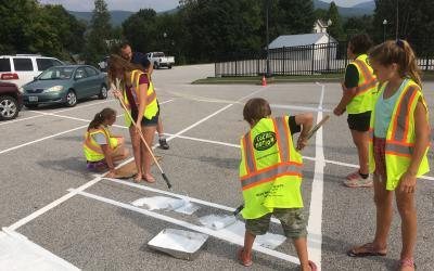 Students paint a crosswalk in a transportation project